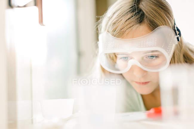 Девушка проводит научный эксперимент, наблюдает через защитные очки — стоковое фото