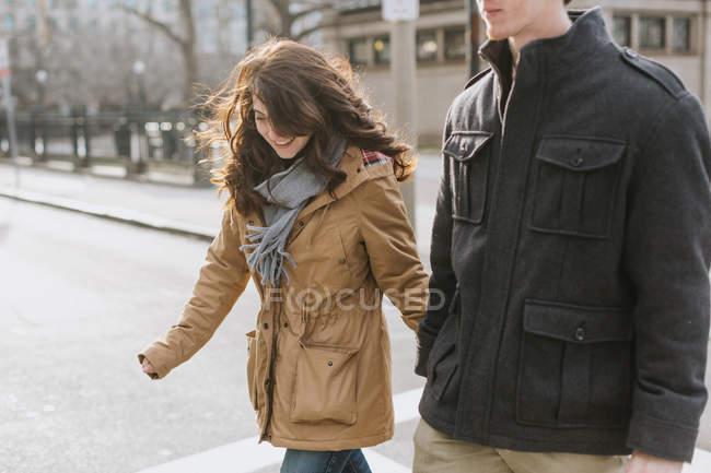 Giovane coppia che attraversa la strada, a metà tratto — Foto stock