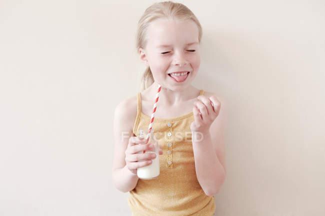 Giovane ragazza attaccare lingua fuori e tenendo il bicchiere di latte — Foto stock