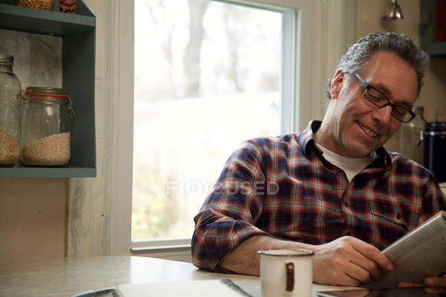 Mature man reading magazine at home — Stock Photo