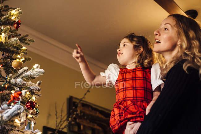Kleinkind mit Mutter zeigt auf Christbaumkugel — Stockfoto