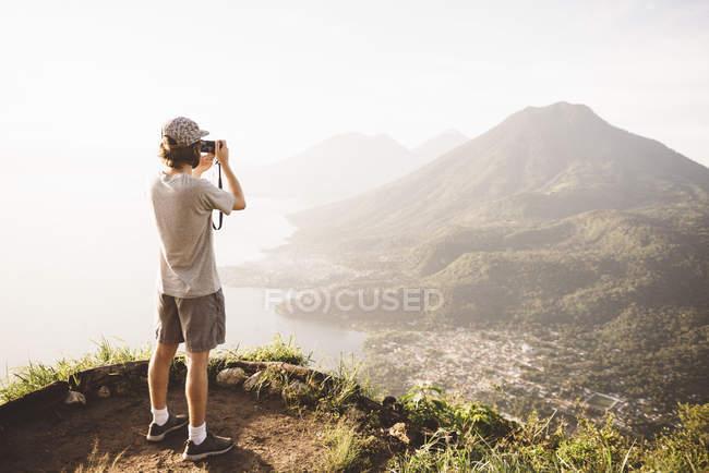 Jeune homme photographiant au lac Atitlan sur un appareil photo numérique, Guatemala — Photo de stock