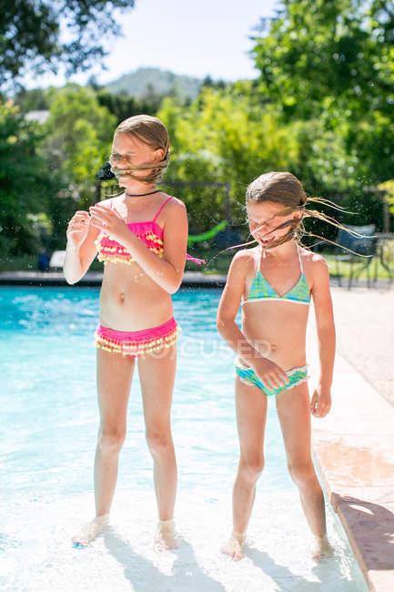 Deux sœurs secouant les cheveux mouillés près de la piscine extérieure — Photo de stock