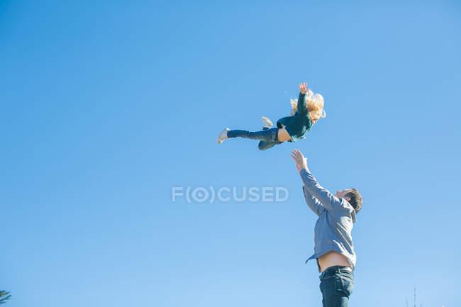 Девушка, которую отец бросает в воздух на голубое небо — стоковое фото