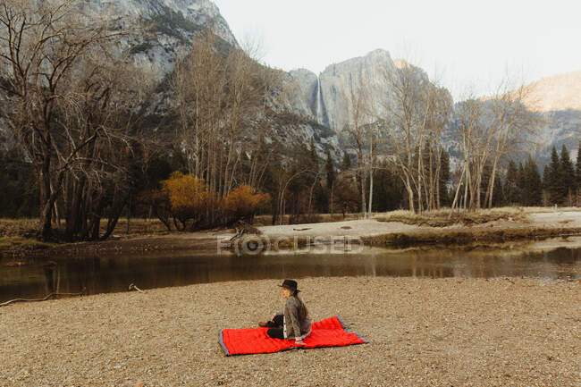 Woman sitting on red blanket looking out at landscape, Yosemite National Park, California, USA — Stock Photo