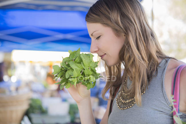 Mujer en puesto de frutas y verduras que huele hierbas frescas - foto de stock