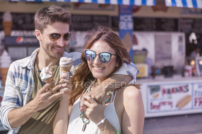 Modern couple having a good time at amusemnt park boardwalk eating soft ice creme — стоковое фото