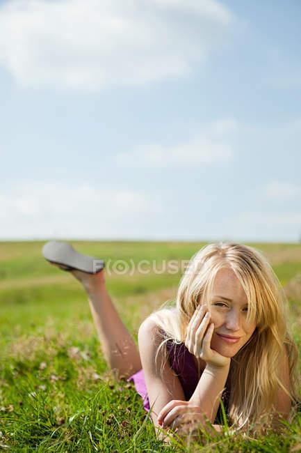 Молодая женщина, лежа на ее передней в поле, улыбаясь — стоковое фото