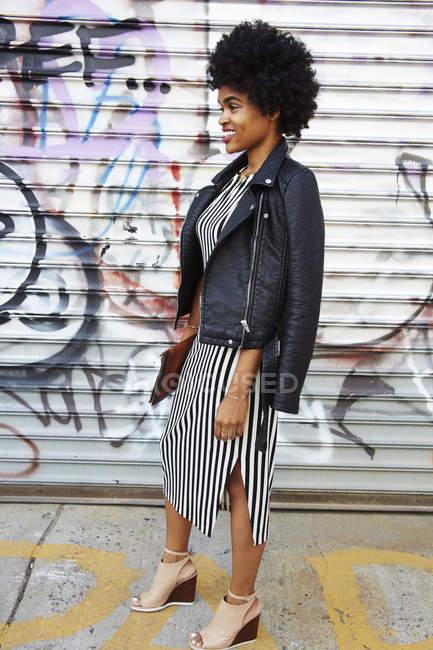 Jovem blogueira de moda feminina com cabelo afro por parede de grafite, Nova York, EUA — Fotografia de Stock