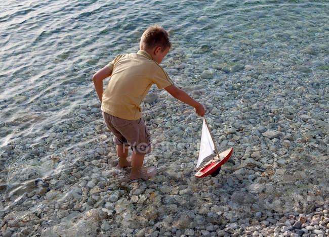 Junge mit spielzeugboot am Strand — Stockfoto