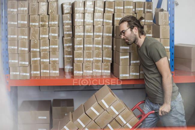 Homme poussant chariot sac de boîtes en carton empilées dans l'usine — Photo de stock