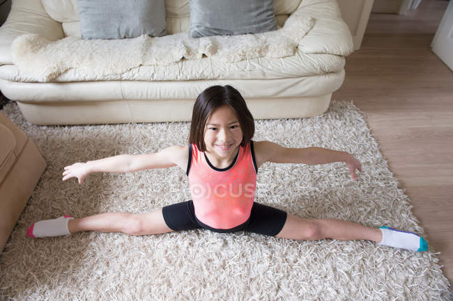 Girl practicing gymnastic splits on living room rug — Stock Photo