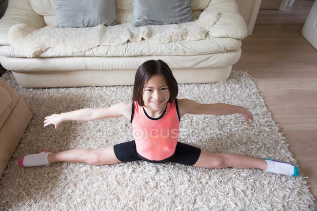 Дівчина практикуючих гімнастичні розпадається на килим вітальні — стокове фото