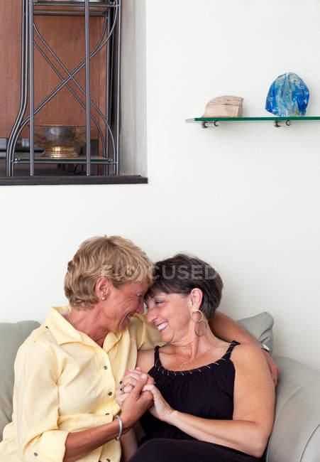 Зрелые лесбиянки, охватывающей на диване — стоковое фото