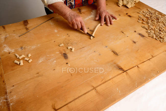 Cropped image of senior woman making pasta from dough — Stock Photo