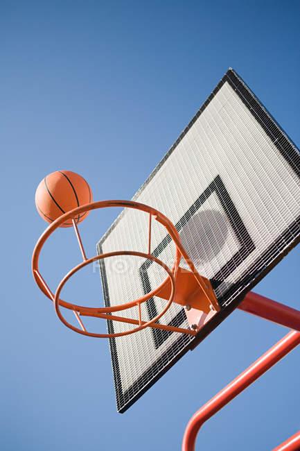 Баскетбольный мяч и обруч на ясном голубом небе — стоковое фото