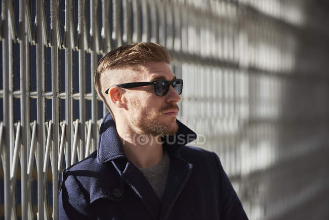 Young man standing beside metal fence, pensive expression — Stock Photo