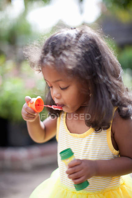 Девушка выдувает пузыри на улице — стоковое фото
