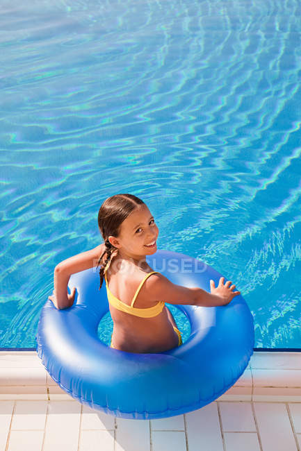 Girl with inflatable ring by swimming pool — Stock Photo
