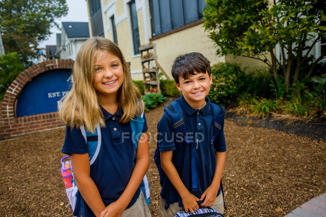 Portrait of male and female twins outside elementary school — Stock Photo