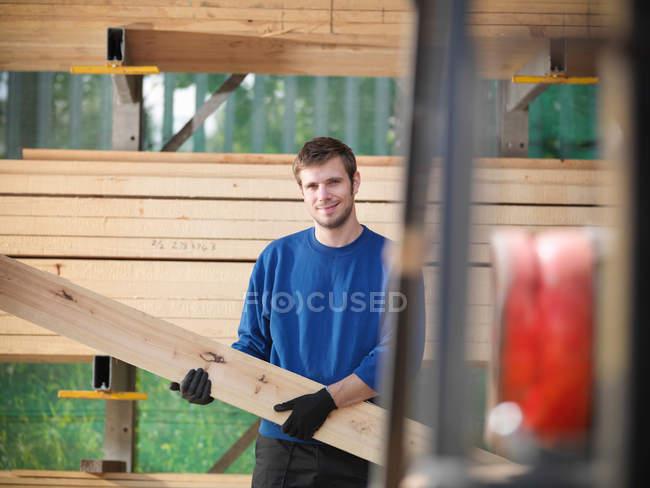 Travailleur tenant des planches de bois en menuiserie — Photo de stock