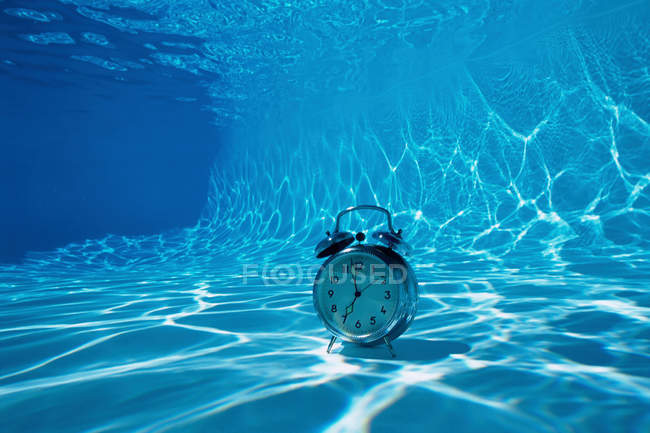 Despertador en la parte inferior de la piscina - foto de stock