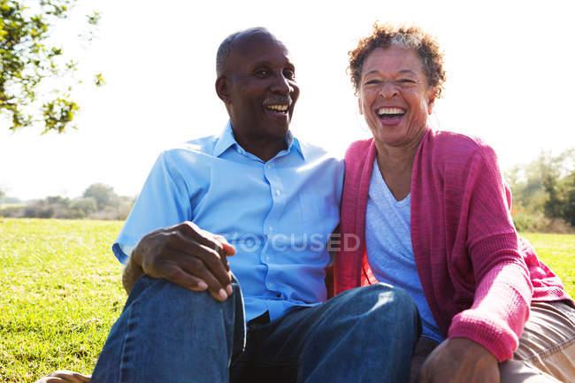 Retrato de casal sênior sentado no parque — Fotografia de Stock