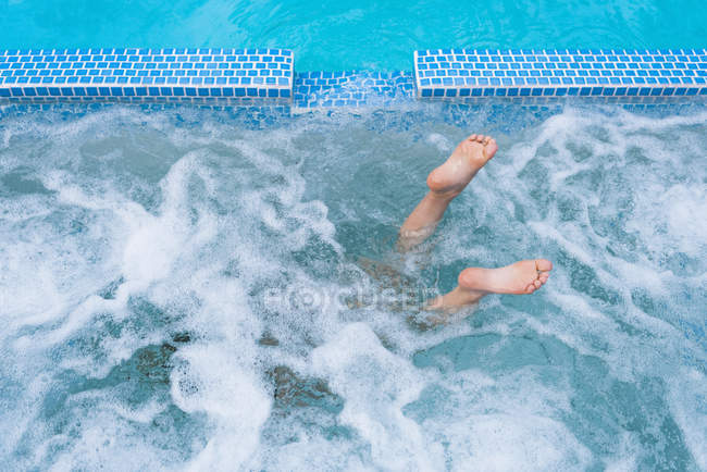Feets out of swiming pool — Stock Photo