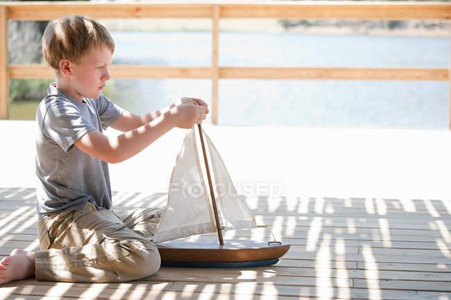 Мальчик играет с игрушечной лодкой — стоковое фото