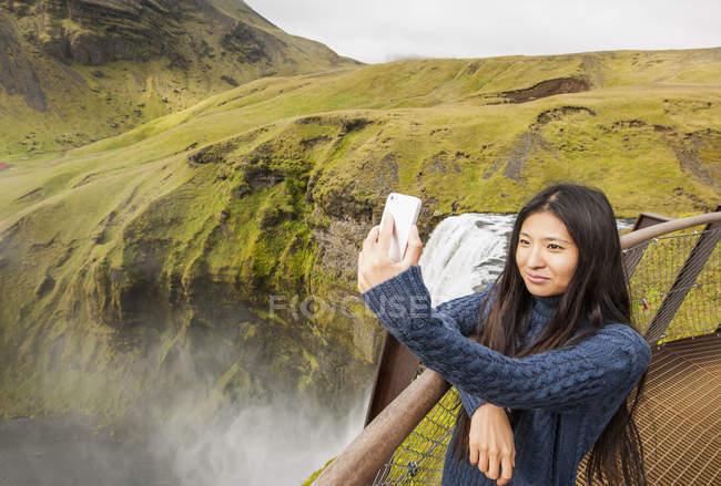Female tourist taking smartphone selfie at Skogafoss waterfall, Iceland — Stock Photo
