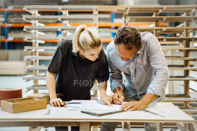 Male carpenter explaining blueprint to female trainee in workshop — Stock Photo