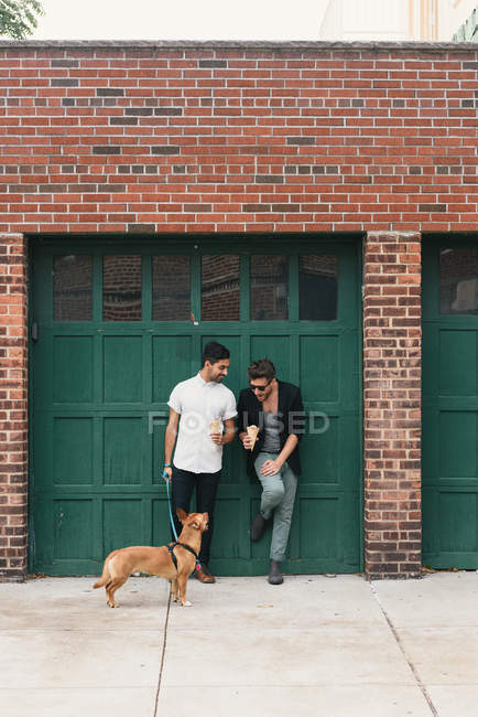 Young male couple with dog leaning on garage eating ice cream cones — Stock Photo