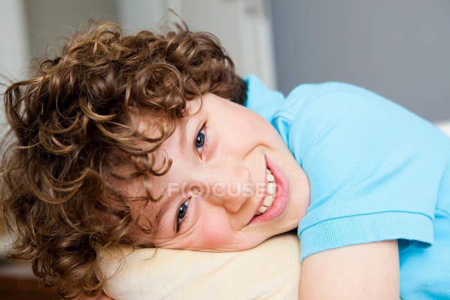 Portrait of Boy with curly hair smiling — Stock Photo