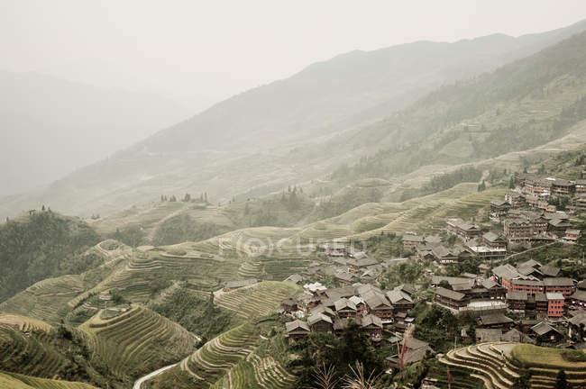 Terrassenfelder und Dorf am Hang — Stockfoto