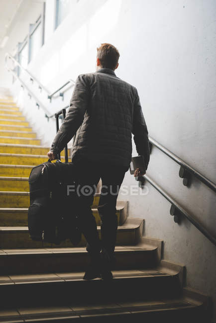 Rear view of young businessman commuter on stairs carrying suitcase. — Stock Photo