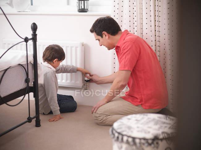 Отец учит сына регулировать термостат на радиаторе в спальне энергоэффективного дома — стоковое фото
