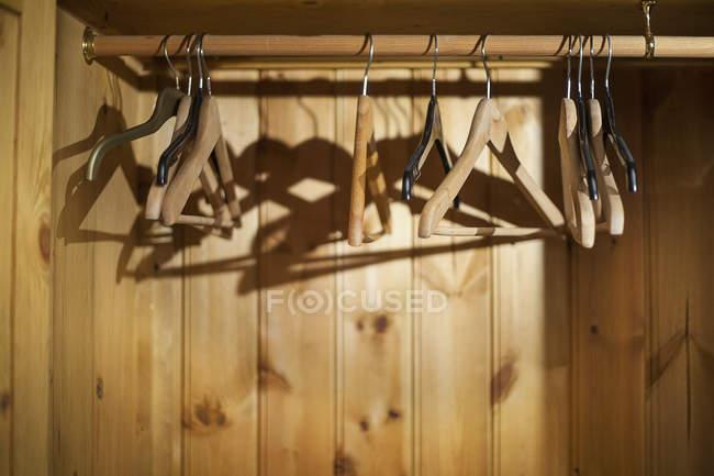 Вішалки для одягу в порожній дерев'яний шафа — стокове фото