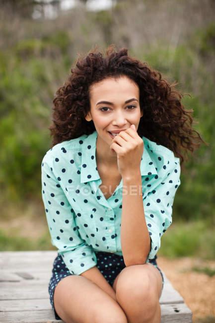 Mujer joven sentada en la mesa de picnic sonriendo, retrato - foto de stock