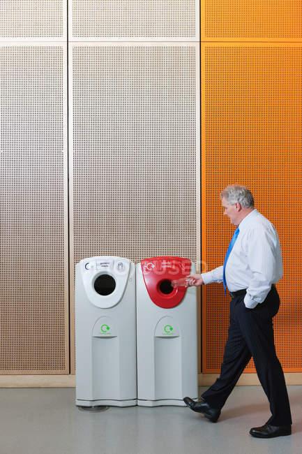 Homme d'affaires jetant la bouteille dans la poubelle de recyclage — Photo de stock