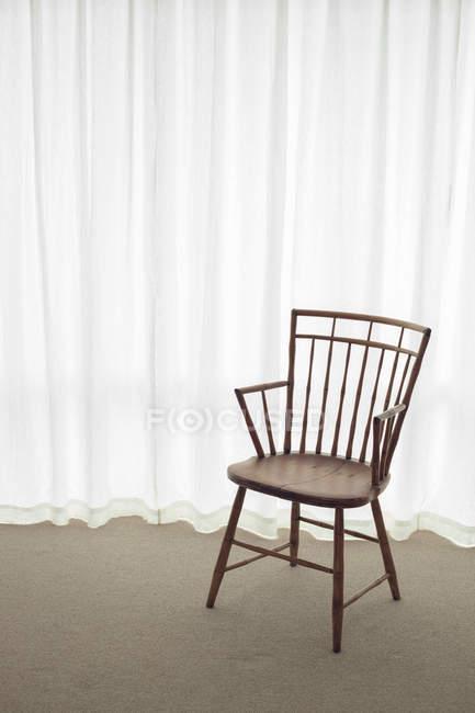 Leere Holzstuhl mit weißen Vorhängen auf Hintergrund — Stockfoto