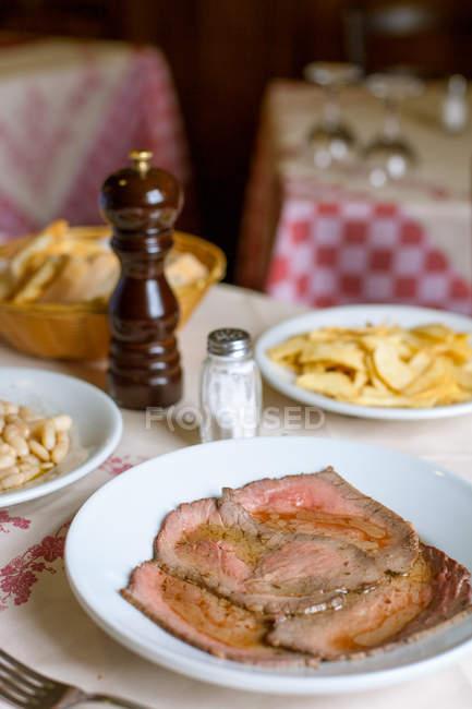 Ресторан пластини ростбіф з білої квасолі і картопля фрі — стокове фото
