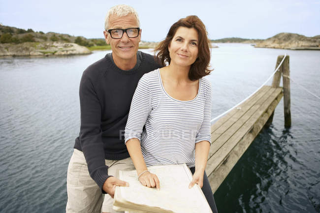 Middle aged couple with map on pier — Stock Photo