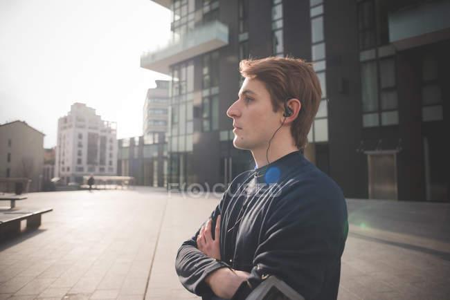 Молодой бегун слушает наушники на городской площади — стоковое фото