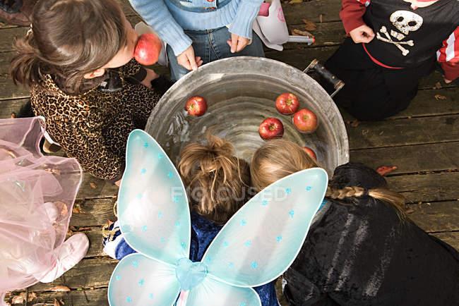 Vista de ángulo alto de los niños bobinado manzana - foto de stock