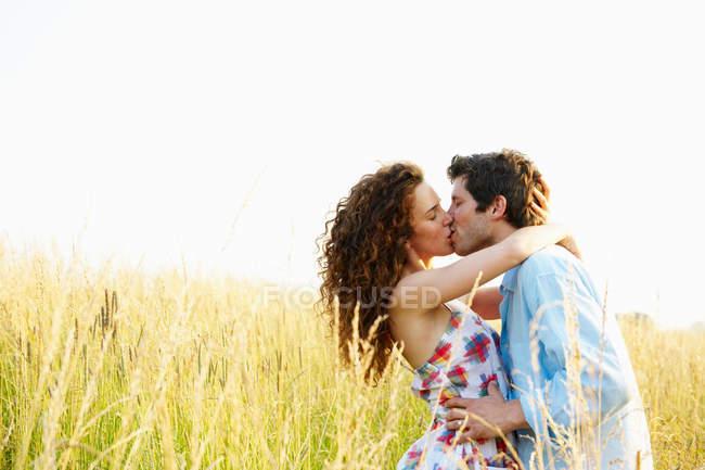 Paar küsst sich in einem Weizenfeld — Stockfoto