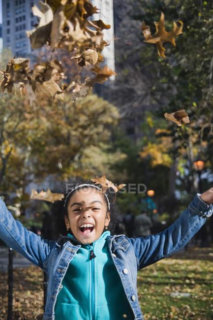 Menina jogando folhas de outono e sorrindo — Fotografia de Stock