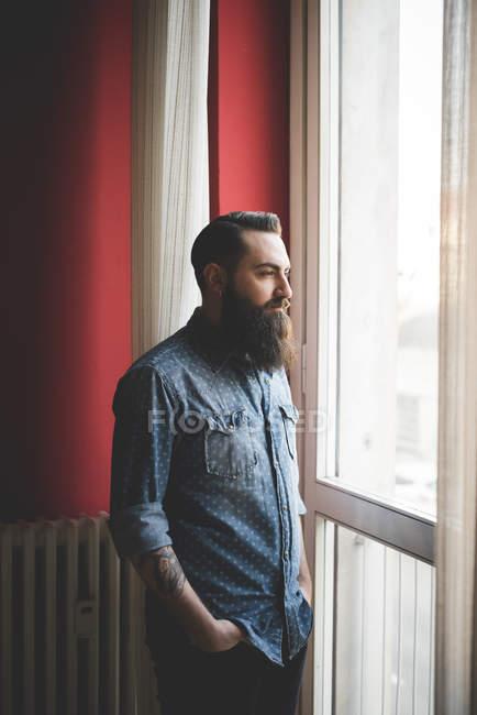 Молодой бородатый мужчина стоит у окна — стоковое фото