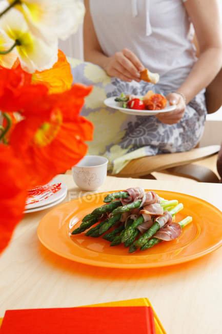 Plate of asparagus with bacon with dining woman in background — Stock Photo