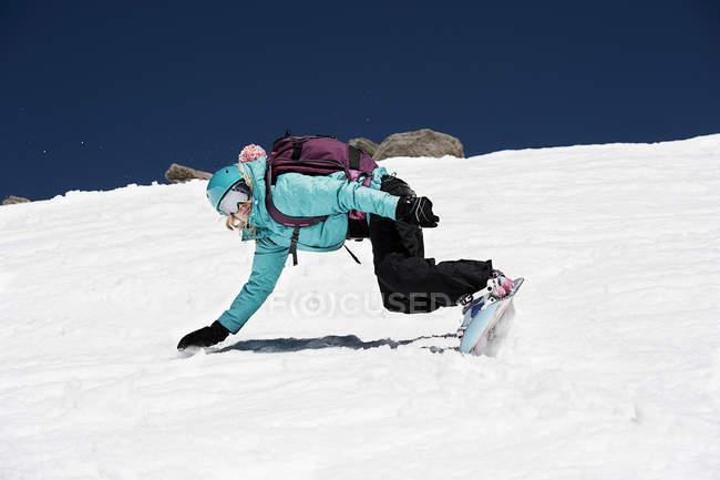 Женщины сноубордист падает на горе — стоковое фото