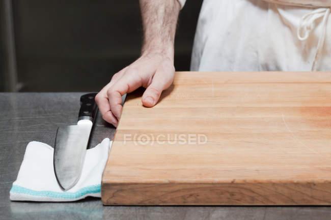 Close-up da mão de açougueiro com tábua e faca — Fotografia de Stock